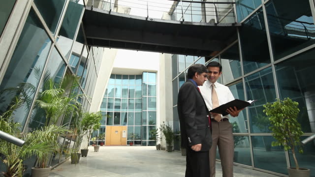 Two businessmen holding a file and discussing