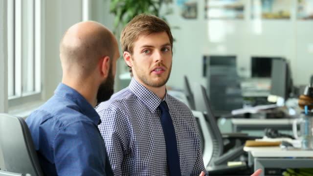 stockvideo's en b-roll-footage met ms two businessmen in discussion during informal project meeting in office workstation - overhemd en stropdas