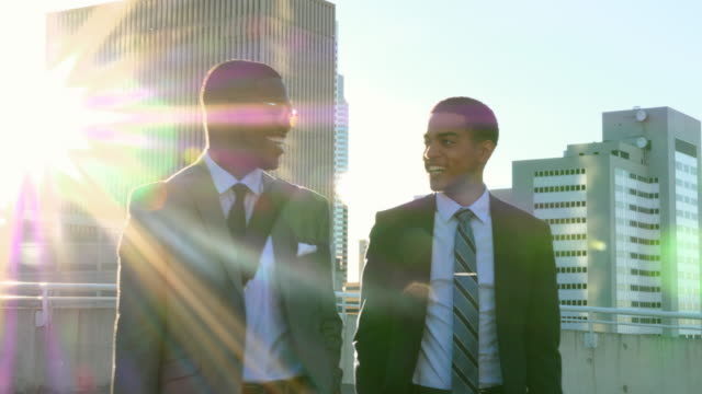 ms ts two businessmen in discussion walking across downtown parking garage at sunrise - two people stock videos & royalty-free footage