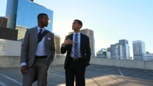 MS TS Two businessmen in discussion while walking on downtown parking garage rooftop