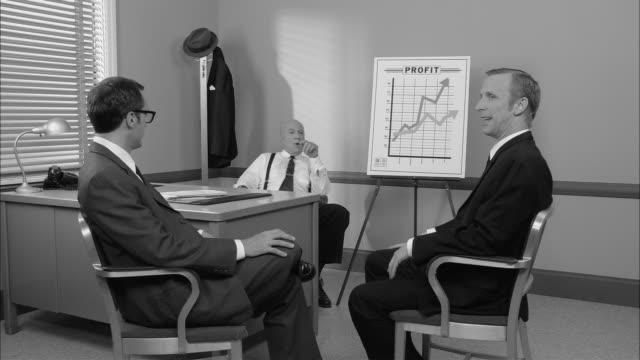 vidéos et rushes de b/w ms two businessmen in meeting with boss about increased profits/ new york city - faire de l'argent
