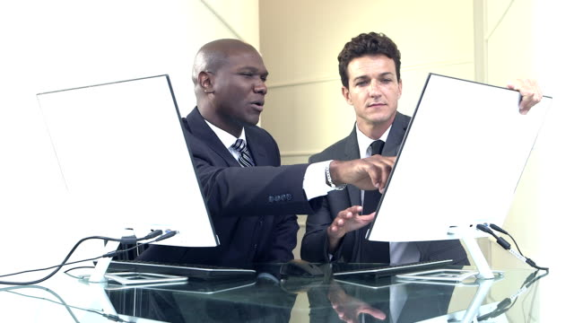 Two businessmen in suits with computers, talking