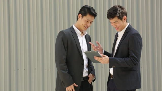 MS Two businessmen looking at a digital tablet in front of a wall.