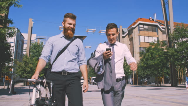 slo mo two businessmen looking at something on a mobile phone in the city - hipster person stock videos & royalty-free footage