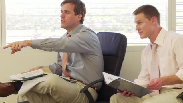 vídeos de stock e filmes b-roll de two businessmen looking through paperwork files - fotografia de três quartos