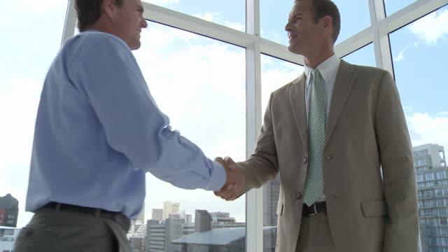 two businessmen meeting in office, shaking hands - 全套西裝 個影片檔及 b 捲影像