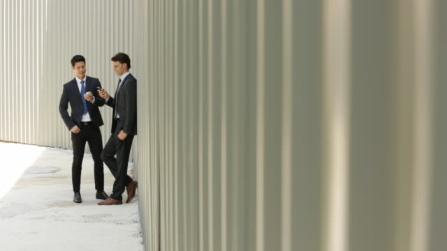 WS Two businessmen on their phones in front of a wall.