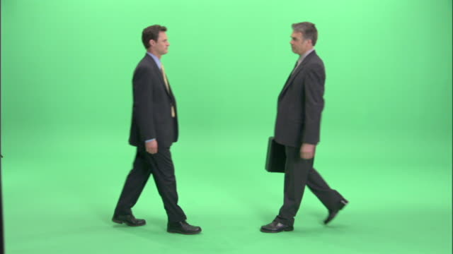ws, two businessmen passing bundle of money and briefcase to each other in studio - suspicion stock videos & royalty-free footage