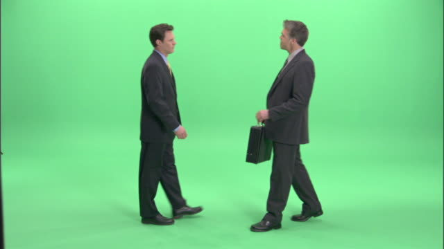 ws, two businessmen passing bundle of money and briefcase to each other in studio - briefcase stock videos & royalty-free footage