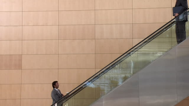 slo mo ws two businessmen passing each other on escalator, cape town, south africa - rolltreppe stock-videos und b-roll-filmmaterial