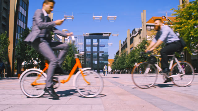 ws two businessmen riding their bicycles in the city - moving past stock videos & royalty-free footage