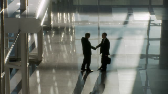 WS HA Two businessmen shaking hands in lobby / Bangkok, Thailand