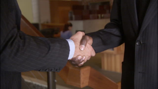 vídeos de stock, filmes e b-roll de cu two businessmen shaking hands in office / los angeles, california, usa - dando a mão