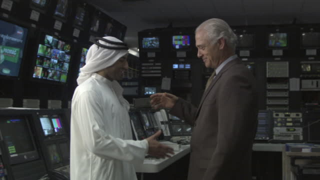 MS Two businessmen shaking hands in television studio control room / Culver City, California, USA