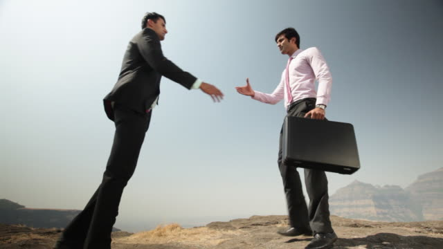vídeos de stock, filmes e b-roll de two businessmen shaking hands on the cliff of mountain  - camisa e gravata