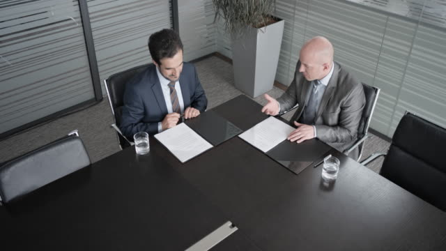 cs two businessmen signing a contract in the conference room - part of a series stock videos & royalty-free footage
