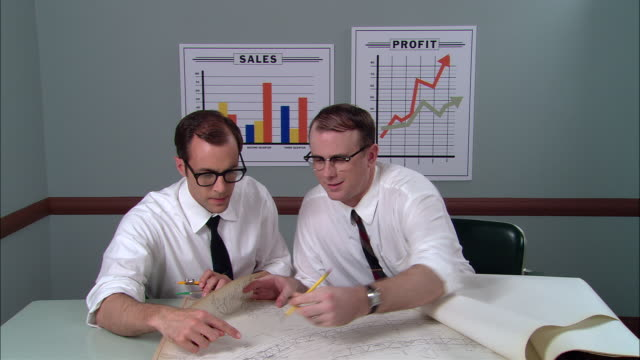 stockvideo's en b-roll-footage met ms two businessmen sitting at table, looking at architectural plans and discussing/ man measuring plans with protractor/ new york city - overhemd en stropdas