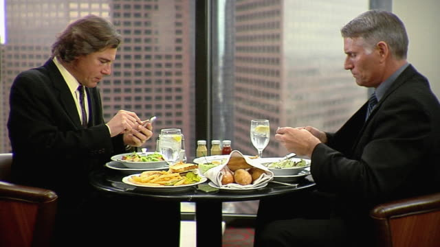vídeos y material grabado en eventos de stock de ms two businessmen sitting at table using mobile phones, los angeles, california, usa - descanso para comer