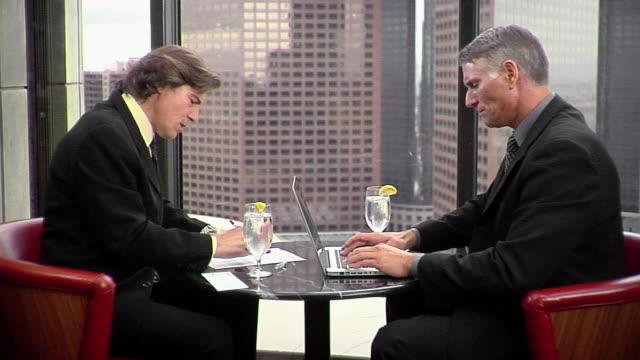 ms two businessmen sitting at table working on laptop, los angeles, california, usa - hel kostym bildbanksvideor och videomaterial från bakom kulisserna