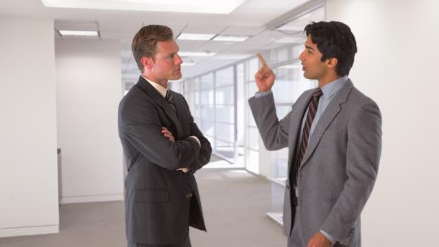 two businessmen standing and talking - abbigliamento da lavoro formale video stock e b–roll
