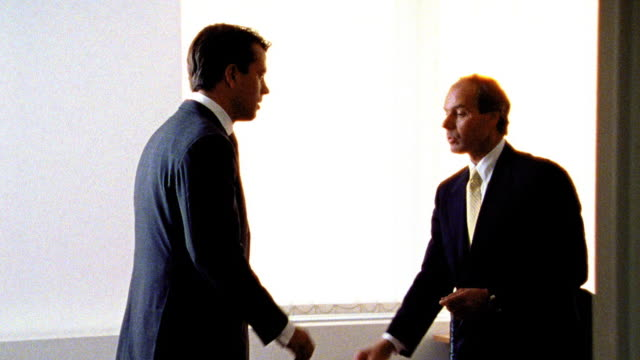 OVEREXPOSED CANTED two businessmen standing at desk talking + shaking hands