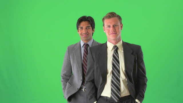 two businessmen standing smiling on greenscreen