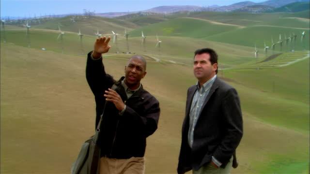 vídeos y material grabado en eventos de stock de ws two businessmen surveying landscape near wind turbines on hill / livermore, california, usa - empresa de carácter social