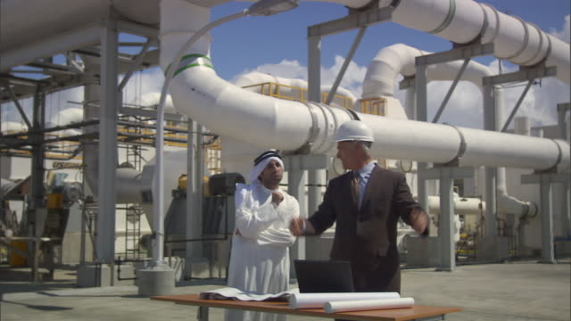 MS Two businessmen talking about blueprint and shaking hands outside oil refinery / Vista del Mar, California, USA