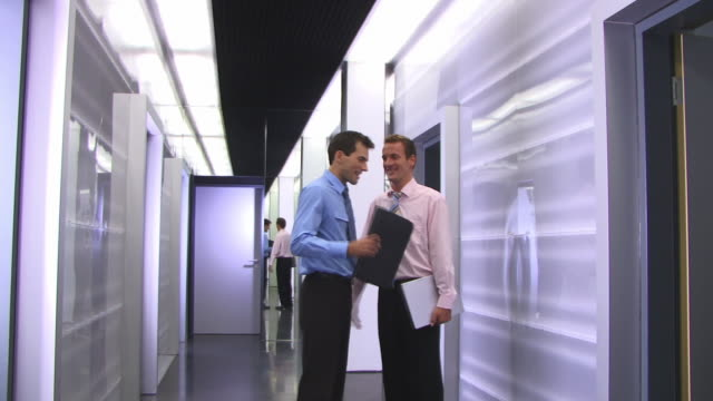 MS, Two businessmen talking in corridor