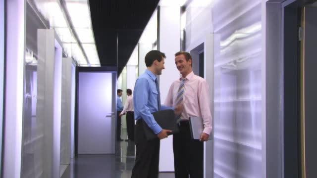 MS, DS, Two businessmen talking in corridor
