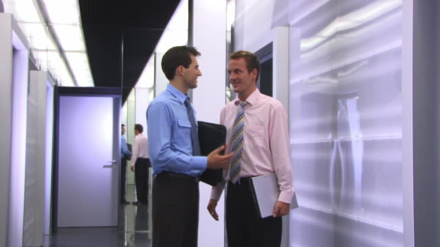 stockvideo's en b-roll-footage met ms, two businessmen talking in corridor - overhemd en stropdas