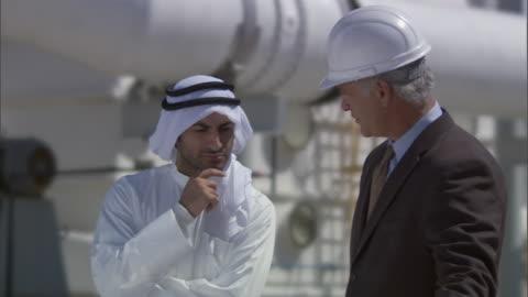 cu two businessmen talking outside oil refinery/ vista del mar, california, usa - long beach california video stock e b–roll