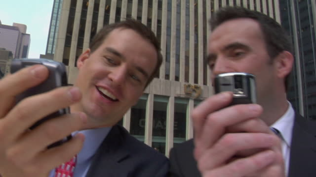 stockvideo's en b-roll-footage met la cu two businessmen text messaging side by side near office building / new york, new york, usa - 30 39 jaar