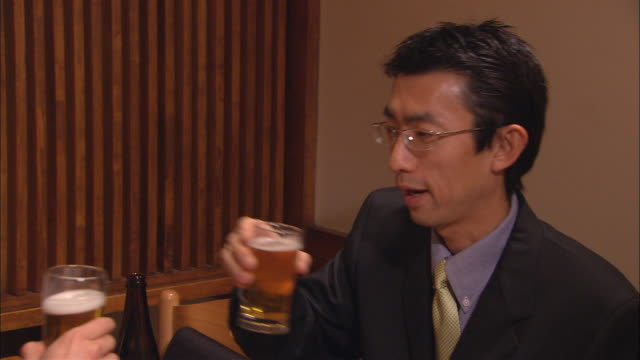 cu, two businessmen toasting with beer in restaurant - 飲む点の映像素材/bロール