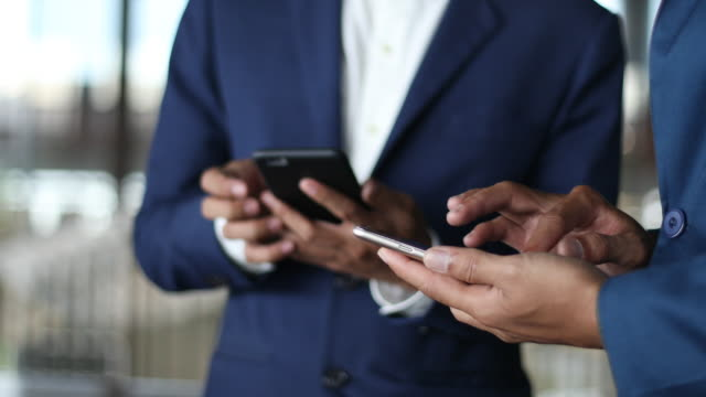 Two Businessmen use smartphone and shaking hand