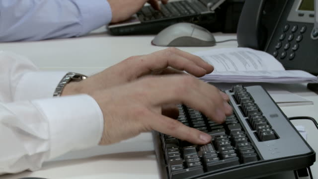 Two businessmen using computer keyboards