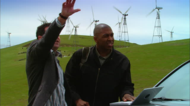 MS Two businessmen using laptop on hood of car + surveying landscape near wind turbines on hill / Livermore, California, USA