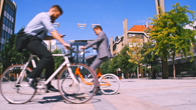 WS Two businessmen using mobile phones while riding a bicycles in the city