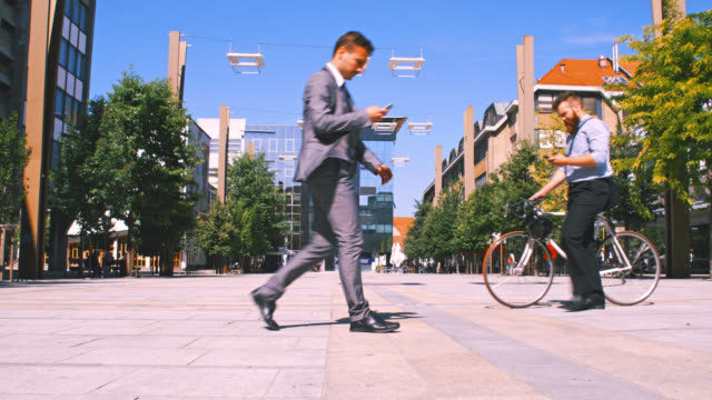 slo mo two businessmen using mobile phones while walking in the city - moving past stock videos & royalty-free footage