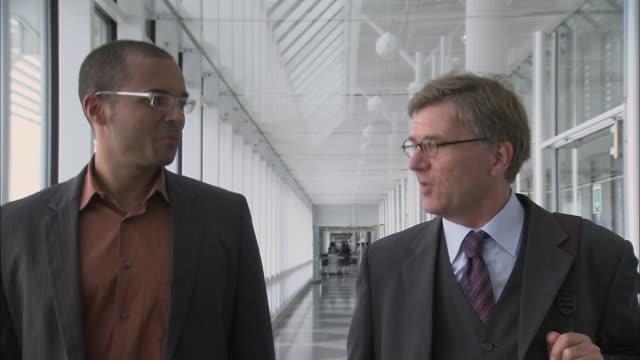 stockvideo's en b-roll-footage met ms ts two businessmen walking down glassy airport corridor/ munich, germany - münchen vliegveld
