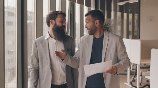 two businessmen walking through the office, engaging in conversation - formal businesswear stock videos & royalty-free footage