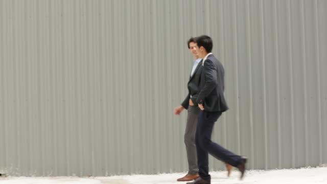 vídeos de stock e filmes b-roll de ws two businessmen walking together in front of a wall. - em frente de