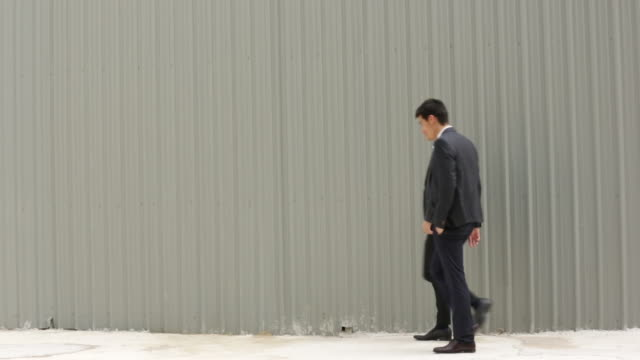 WS Two businessmen walking together in front of a wall.
