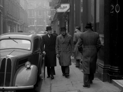 vídeos de stock e filmes b-roll de two businessmen wearing bowler hats enter a building. 1955. - enfeites para a cabeça