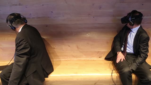 vidéos et rushes de two businessmen wearing suits sit on a bench using virtual reality headsets at the volvo cars stand at the paris motor show on the final preview day... - casque téléphonique