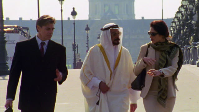 two businessmen (1 arab) + woman walking toward camera on pont alexandre iii / les invalides in background - female with group of males stock videos & royalty-free footage