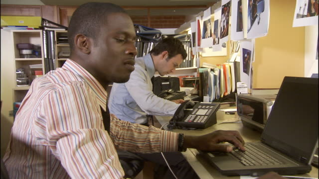 CU Two businessmen working in crowded office / Los Angeles, California, USA