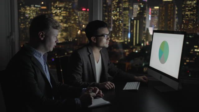 two businessmen working late in office. discussing profits with computer monitor. graphs, charts and city light background. - working overtime stock videos & royalty-free footage