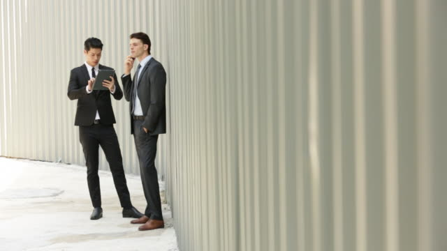WS Two businessmen working on digital divices in front of a wall.
