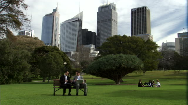ws, two businessmen working on laptop in park, office buildings in background, sydney, australia - ベンチ点の映像素材/bロール